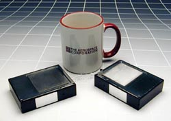 Picosatellites, less than one-half pound each, are shown against a coffee mug. The Aerospace Corporation.