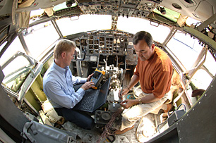 Mike Dinallo and Larry Schneider (left) prepare to employ the PASD diagnostic on a wiring bundle in the cockpit of a retired Boeing 737 at Sandia's FAA Airworthiness Assurance NDI Validation Center. (Photo by Randy Montoya)