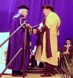 Neil Lewis (right) is pictured here receiving his Honorary Degree from the University Chancellor Lord Morris