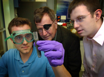 Purdue researchers demonstrate their method for producing hydrogen by adding water to an alloy of aluminum and gallium. The hydrogen could then be used to run an internal combustion engine or a fuel cell. The reaction was discovered by Jerry Woodall, center, a distinguished professor of electrical and computer engineering. Charles Allen, holding test tube, and Jeffrey Ziebarth, both doctoral students in the School of Electrical and Computer Engineering, are working with Woodall to perfect the process. (Purdue News Service file photo/David Umberger)