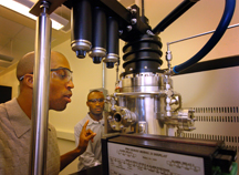 "Mechanical engineering doctoral student Baratunde A. Cola, from left, looks through a view port in a plasma-enhanced chemical vapor deposition instrument while postdoctoral research fellow Placidus Amama adjusts settings. The two engineers recently have shown how to grow forests of tiny cylinders called carbon nanotubes onto the surfaces of computer chips to enhance the flow of heat at a critical point where the chips connect to cooling devices called heat sinks. The carpetlike growth of nanotubes has been shown to outperform conventional ""thermal interface materials."" The research is based at the Birck Nanotechnology Center in Discovery Park at Purdue. (Purdue News Service photo/David Umberger)"