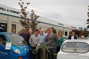 Taylor Smith cuts the green ribbon for a new ZAP electric car dealership that opened today in Silicon Valley. San Carlos Mayor Tom Davis to his left and the Chamber of Commerce welcomed the new business and tried out the new electric cars, trucks, scooters, and mopeds from Bay Area electric vehicle manufacturer ZAP.