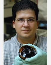 Chemical engineer Carlos Rinaldi holds a beaker with oil based ferrofluid (a suspension of magnetic nanoparticles in an oil carrier fluid) with a permanent magnet underneath. The ferrofluid displays the so-called normal field instability, characterized by spikes of fluid following the local magnetic field direction. Rinaldi's work has importance for applications in nanobiosensors and in magnetic fluid hyperthermia for cancer treatment.