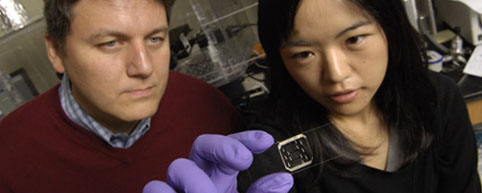 Andre Levchenko with graduate student Hojung Cho holding innovative device with microscopic chambers. Credit: Will Kirk / JHU
