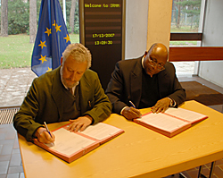 Alejandro Herrero, director of the European Commission's Joint Research Centre Institute for Reference Materials and Measurements (JRC IRMM), and NIST Chemical Science and Technology Laboratory Director Willie May sign a pact in Belgium on Dec. 17, 2007, to advance the development and availability of international measurement standards in the fields of chemistry, life sciences and emerging technologies.