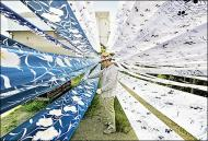 A craftsman spreads his fabric out to dry