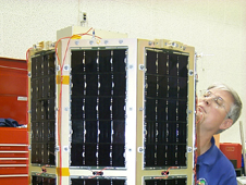 Dr. Billy R. Smith Jr., director of the USNA Small Satellite Program and MidSTAR-1 program manager, inspects MidSTAR-1 for damage after vibration testing at the Naval Research Laboratory. This test demonstrated that the satellite could survive the rigors of launch and retain functionality. High-efficiency, triple-junction gallium arsenide solar cells cover the sides; the S-band transmit antenna is visible at the upper right. The external neutron detector for the MicroDosimeter Instrument (MiDN) is visible on the top. Credit: USNA