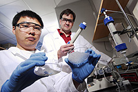 Researchers Kurt Pennell (standing) and Younggang Wang examine glass microbeads and sand used to study the transport and retention of C60 particles in water. (Georgia Tech Photo: Gary Meek)