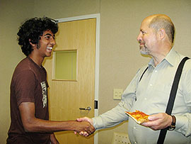 New NanoExplorer Anish Jacob shares pizza and a handshake with Dr. Ray Baughman, who founded the NanoExplorers program.