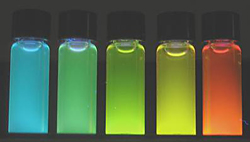 Brightly glowing vials of highly luminescent, water soluble quantum dots produced by the new NIST microwave process span a wavelength range from 500 to 600 nm.