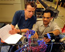 "Researchers at Purdue are developing a miniature refrigeration system small enough to fit inside laptops and personal computers, a cooling technology that would boost performance while shrinking the size of computers. The researchers collect data using a myriad of sensors to precisely measure how a refrigerant boils and vaporizes inside tiny ""microchannels"" in a part of the refrigeration system called an evaporator. Data are needed to determine how to vary this boiling rate for maximum chip cooling. Eckhard Groll, at left, a professor of mechanical engineering, and Suresh Garimella, the R. Eugene and Susie E. Goodson Professor of Mechanical Engineering, discuss the microchannel data at the Ray W. Herrick Laboratories. (Purdue News Service photo/David Umberger)"