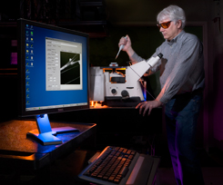 Sandia researcher Carl Hayden positions a sample on the spectrally resolved, confocal imaging microscope.