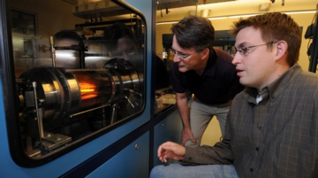 "Timothy D. Sands, at left, director of Purdue's Birck Nanotechnology Center in Discovery Park, and graduate student Mark Oliver, operate a ""reactor"" in work aimed at perfecting solid-state lighting, a technology that could cut electricity consumption by 10 percent if widely adopted. Inside the reactor, a material called gallium nitride is deposited on silicon at  temperatures of about 1,000 degrees Celsius, or 1,800 degrees Fahrenheit. Purdue researchers have overcome a major obstacle in reducing the cost of the lighting technology, called light-emitting diodes . (Purdue News Service photo/David Umberger)"