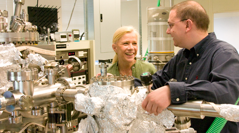 VMEC Associate Professor Ale Lukaszew (left) works with César Clavero, a post-doctoral research associate in applied science, in their lab in McGlothlin-Street Hall. Clavero says that the aluminum foil covering parts of their vacuum pump makes an excellent insulator. He recently won an Outstanding Young Researcher Award from the American Vacuum Society.