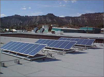 Solar power collectors, like these photovoltaic panels on a New Mexico high school roof, could be installed much more widely if they could be manufactured from less-costly materials. (U.S. Department of Energy photo)