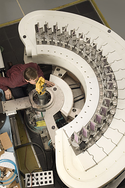 Top view of the MACS multiaxis detector system (seen before being enclosed in shielding material). With more neutrons striking the sample and more detectors surrounding it, MACS will greatly extend the capabilities of neutron inelastic scattering as a materials probe technique in nanotechnology and basic science. Principal investigator Collin Broholm of the Johns Hopkins University is seen examining the alignment of one of the 20 detection channels.