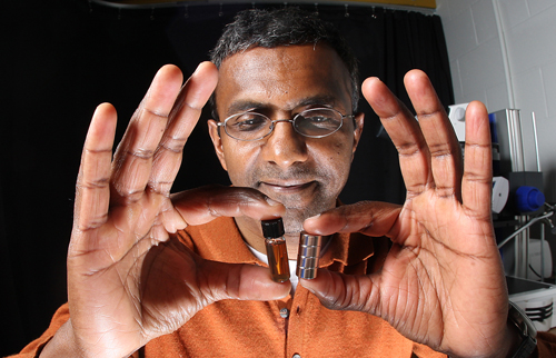 Purdue professor Joseph Irudayaraj uses a magnet to attract tiny magnetic particles in a solution. Irudayaraj designed nanoprobes with gold and magnetic particles that could be used to deliver drugs directly to cancer cells. (Purdue Agricultural Communication photo/Tom Campbell)