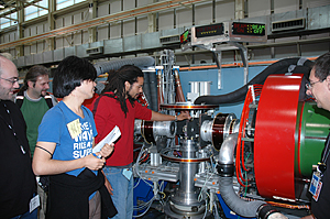 Khiza Mazwi, a student from the University of Southern California, replaces a sample in the spin echo spectrometer while other participants in the NCNR summer school look on.