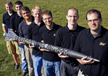 "Purdue is working with NASA, the Air Force Office of Scientific Research and Pennsylvania State University to develop a new type of rocket propellant made of a frozen mixture of water and ""nanoscale aluminum"" powder. The propellant, called ALICE, is more environmentally friendly and could be manufactured on the moon, Mars and other water-bearing bodies. Holding a rocket launched earlier this year using the propellant, from left, are: mechanical engineering undergraduate student Cody Dezelan, mechanical engineering graduate student Tyler Wood, mechanical engineering professor Steven Son, aeronautics and astronautics graduate student Mark Pfeil, mechanical engineering doctoral student Travis Sippel, aeronautics and astronautics research assistant professor Timoth�e Pourpoint, and postdoctoral researcher John Tsohas. (Purdue University photo/Andrew Hancock)"