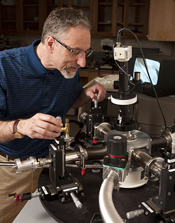 In his Johns Hopkins materials science lab, Howard E. Katz adjusts probes used for testing electronic devices. Photo by Will Kirk, Homewoodphoto.jhu.edu.