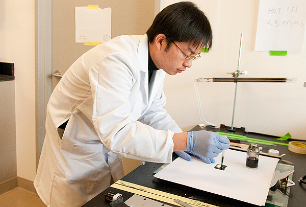 Bing Hu, a post-doctoral fellow, prepares a small square of ordinary paper to with an ink that will deposit nanotubes on the surface that can then be charged with energy to create a battery.