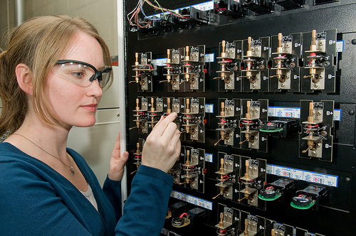 Argonne researcher Lynn Trahey loads a coin-sized cell on a testing unit used to evaluate electrochemical cycling performance in batteries. Photo by Wes Agresta / Courtesy Argonne National Laboratory.