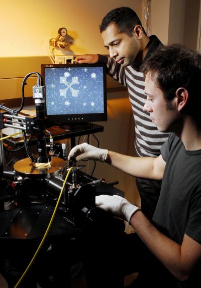 Researchers Raghunath Murali and graduate student Kevin Brenner(front) perform electrical measurements on a graphene sample under high vacuum in a cryogenic probe station.  Credit: Georgia Tech Photo: Gary Meek