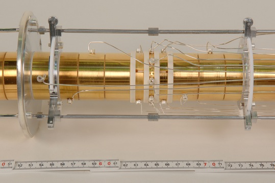 The picture shows the Penning trap, which is part of the Shiptrap experiment. A magnetic field parallel to the tube forces the arriving ions onto a spiral course inside the tube. The ions� spiraling frequency is used to directly calculate their atomic mass.