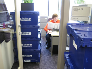 Lisa Kiel, office manager for U-M's Institutional Review Boards, is surrounded by boxes at her new office at the North Campus Research Complex. Kiel and about 30 other IRB employees will work in their new offices at NCRC for the first time today.