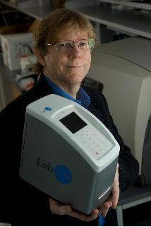 Rice Professor John McDevitt holds the LabNow device to read nano-bio-chips that will look for signs of oral cancer and other diseases. By Jeff Fitlow.