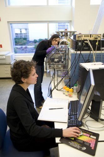 Bindley Bioscience Center researchers Allison Dill, in foreground, and Livia Eberlin analyze molecular fingerprint signatures gathered from a miniature mass spectrometer combined with a technique called desorption electrospray ionization, known as DESI. The device and technique, developed by team led by Purdue professor R. Graham Cooks, will be an essential research tool for the planned Multidisciplinary Cancer Research Facility. (Purdue University photo/Vincent Walter)