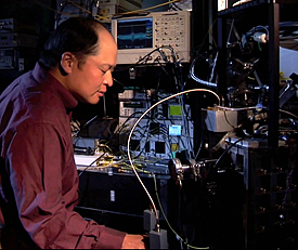 NIST physicist Sae Woo Nam works with refrigeration equipment used to cool photon detectors to nearly absolute zero. His team�s efforts have created devices that can detect single photons with 99 percent efficiency. Credit: NIST
