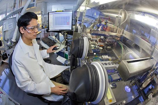 Emory Chan, with Berkeley Lab�s Molecular Foundry, directs WANDA, a revolutionary nanocrystal-making robot, to perform complex workflows that traditionally require extensive chemistry experience. (Photo by Roy Kaltschmidt, Berkeley Lab Public Affairs)