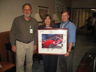 From left, Tom Erickson, chief, Reliability, Availability and Maintainability Engineering & System Assessment Division; Patti Martin, director, Engineering Directorate; and Kris Walker, RAM & SA team lead/Attack & Unmanned Aerial Systems, display a photograph of the No. 61 Roush Performance Products Ford Mustang GT autographed by the Roush-Fenway Racing Team.