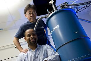 Rice University Professor Junichiro Kono, standing, and graduate student Thomas Searles set out to study interactions between magnetic fields and electrically charged particles and found that strong magnets can stop the flow of electrons through metallic single-walled carbon nanotubes. (Credit Jeff Fitlow/Rice University)