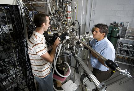 "Purdue nuclear engineering doctoral student Chase Taylor, at left, and Jean Paul Allain, an assistant professor of nuclear engineering, are using this facility in work aimed at developing coatings capable of withstanding the grueling conditions inside nuclear fusion reactors. The research focuses on the ""plasma-material interface,"" a crucial region where the inner lining of a fusion reactor comes into contact with the extreme heat of the plasma. (Purdue University photo/Mark Simons)"