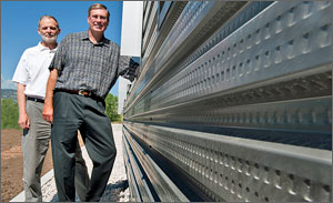 NREL's Craig Christensen and Chuck Kutscher stand next to a wall at the RSF that uses their award-winning transpired air collector technology. Credit: Dennis Schroeder