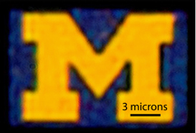 An optical microscopy image of a 12-by-9-micron U-M logo produced with this new color filter process. The image is a bit blurry because it has been magnified about 5,000 times. Credit: Jay Guo.