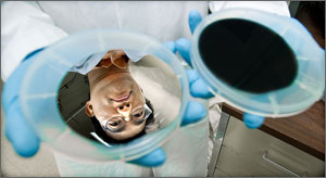 A silver wafer reflects the face of NREL research scientist Hao-Chih Yuan, before the wafer is washed with a mix of acids. The acids etch holes, absorbing light and turning the wafer black. Credit: Dennis Schroeder