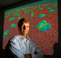 Sandia researcher Matt Lane stands before computer simulations of 2-nm. gold particles too small to measure experimentally. The particles aggregate to produce cigar-shaped objects that prefer to sit at the water�s surface. Red represents oxygen, blue carbon, white hydrogen, yellow the sulfur coating. The gold particles are not modeled directly. (Photo by Randy Montoya)