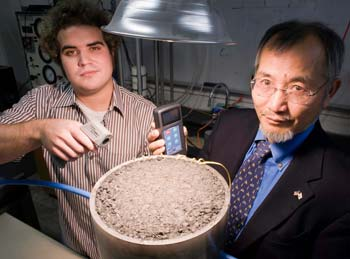 URI student Andrew Correia and Professor K. Wayne Lee conduct a laboratory experiment to measure the solar energy generated by a patch of asphalt. URI Department of Communications & Marketing photo by Michael Salerno Photography.