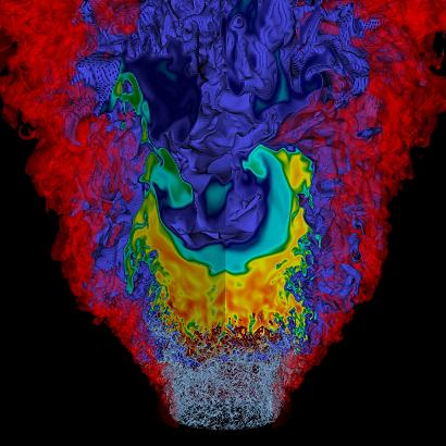 Simulation of a lean hydrogen-air mixture burning in a low-swirl injector. The colors indicate the presence of nitric oxide emissions near the highly wrinkled flame, while the gray structures at the flame base show the turbulent vorticity generated near the breakdown of the swirling flow from the injector.