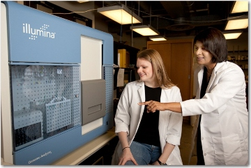 A strong proponent of student success, Preethi Gunaratne is pictured with one of the many students from her lab. Here, she points out the Illumina Genome Analyzer, a key piece of equipment used in her research, to graduate student Ashley Benham. (Photo by Thomas Campbell)