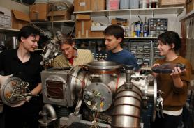 Graduate student Vincent Lonij (left), associate professor of physics Alex Cronin, research assistant Will Holmgren and undergraduate student Catherine Klauss perform maintenance on a chamber used to beam atoms through a grating to measure a tiny force that helps physicists better understand the structure of atoms. (Photo by Norma Jean Gargasz/UANews)