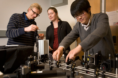 Ulrich Wiesner, left, works with graduate students Jennifer Drewes and Kai Ma to characterize the size and brightness of C dots in their Bard Hall lab. Credit Jason Koski/University Photography
