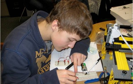 "Chassell High School student Jared Jarvi working on the wiring of a ""bread board"" for a light sensor array. Part of INANO's Lego model is shown."