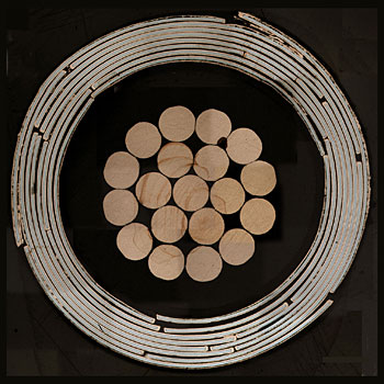Cross-section of a high-temperature superconducting cable design invented at NIST. In the center are copper wires bundled with nylon and plastic insulation. The outer rings are a series of superconducting tapes wrapped in spirals around the copper. The cable is 7.5 millimeters in outer diameter.