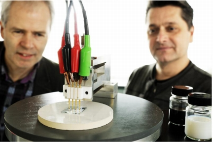 4-point conductivity measurement of the new transparent conducting film developed by prof. Cor Koning (left) and prof. Paul van der Schoot (right). The black pot contains a dispersion of carbon nanotubes in water, and the white pot contains the conducting latex. Photo: Bart van Overbeeke.