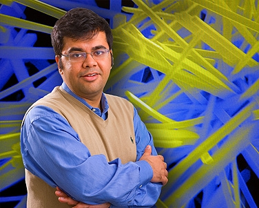 Sarbajit Banerjee stands in front of a scanning electron microscopy image of tungsten-doped vanadium-oxide nanowires, which have a phase transition temperature close to room temperature. Photo: DOUGLAS LEVERE