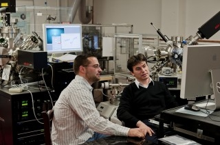 Doctoral student Benjamin Gray, left, and Jak Chakhalian in the laboratory with a unique state-of-the-art piece of equipment built last summer to fabricate atomic layers of complex oxides.